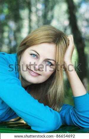 Beautiful blue-eyed smiling woman against blurred forest background with selective focus - stock photo