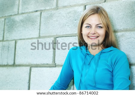Beautiful blue-eyed smiling woman against stone wall with selective focus and copy space - stock photo