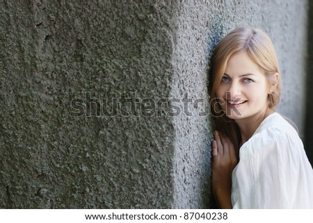 Beautiful blue-eyed smiling woman in blue against rough stone wall with selective focus and copy space - stock photo