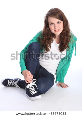 Beautiful blue eyes of a high school teenager girl with long brown hair wearing blue jeans and green jumper with big happy smile. Studio shot against white background.