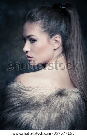 beautiful blue eyes young woman with artificial fur portrait in studio, profile - stock photo