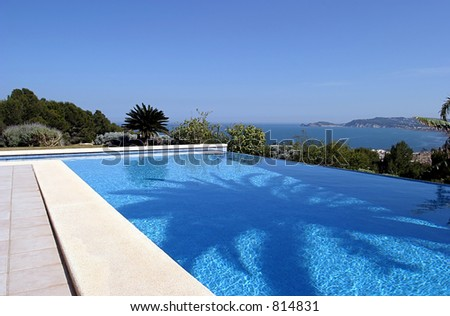 Beautiful blue fresh infinity swimming pool in a villa in sunny Spain with sea views. Has a shadow from a palm tree in the center of the pool.