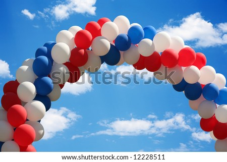 Beautiful blue heavenly and soft cloudy sky with a patriotic balloon arch - stock photo