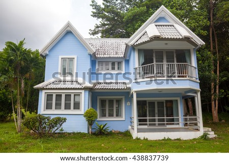 Beautiful blue house green grass and big tree in forest