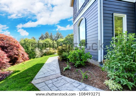 Beautiful Blue house side with walkway and green landscape. - stock photo