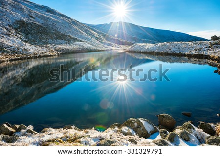 Beautiful blue lake in the mountains, morning sunrise time. Landscape with snow shining sun - stock photo
