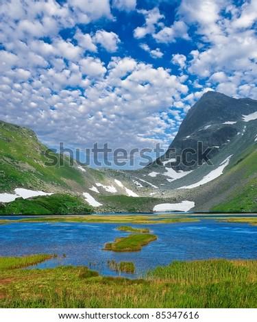 beautiful blue lake near a rocky mountains - stock photo