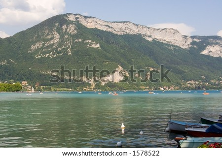 Beautiful blue lake with boats, and mountain background. Annecy, France - stock photo