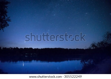 Beautiful blue night sky with many stars on a lake with forest on the other coast. Milkyway reflection in water - stock photo