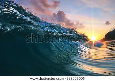 Beautiful blue ocean surfing wave under sunset - stock photo