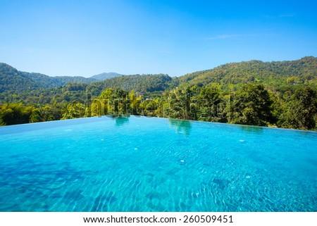 Beautiful blue pool overlooking mountain landscape - stock photo
