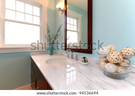 Beautiful blue remodeled bathroom with white marble. - stock photo
