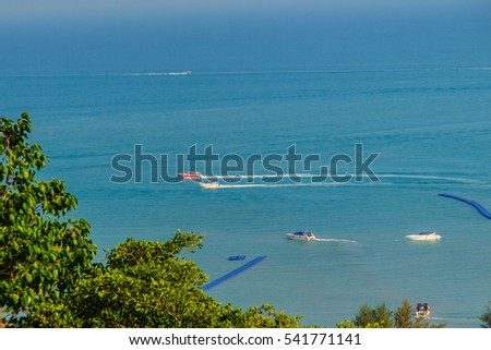 Beautiful blue sea view and tourist water activities such as boat racing, yacht cruising and jet skiing on Koh Sire beach. This picture took from top of Wat Sire temple hill, Phuket city, Thailand.