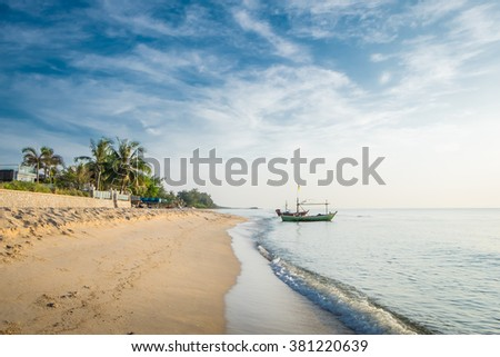 Beautiful blue sea wave and fishing boat on white sand beach for vacations in Hua Hin, Prachuap Khiri Khan Province, Thailand. - stock photo