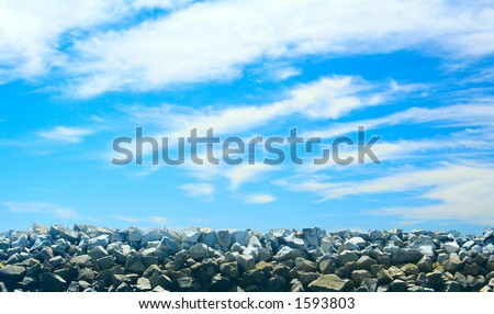 Beautiful blue sky against rocky pier at low tide. - stock photo