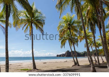 Beautiful blue sky day with a blue sea and empty sand. Playa Samara, Costa Rica, Central America. - stock photo