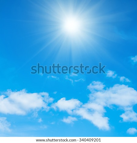 Beautiful blue sky, fluffy white clouds and shining sun with rays - stock photo