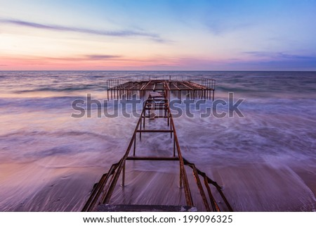 Beautiful blue sky just before the sunrise reflected on wet sandy beach with a pier on background. Long exposure. - stock photo