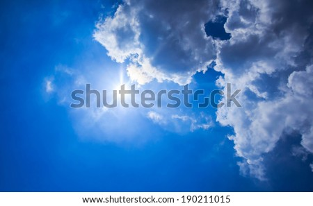 Beautiful blue sky with sunbeams and clouds. Sun rays. - stock photo