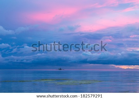 Beautiful blue twilight sunset in the Philippines with the pink, blue and purple colors in the sky reflected in the calm tranquil ocean below against a backdrop of a volcanic mountain peak - stock photo