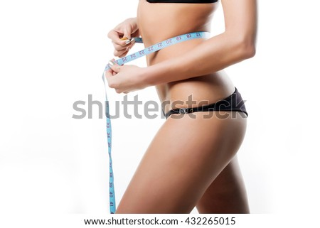 beautiful body of a woman with a measuring tape on a white background - stock photo