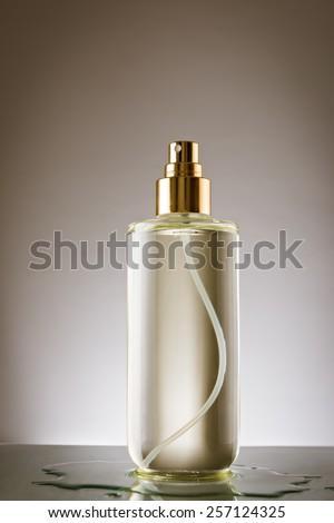 Beautiful bottle of liquid on reflective surface - stock photo