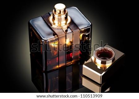 beautiful bottle of perfume on a dark background - stock photo