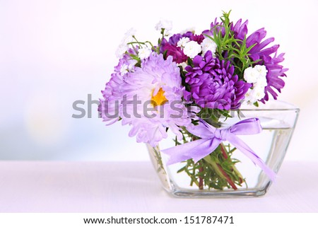 Beautiful bouquet of bright flowers in glass vase, on wooden table, on bright background - stock photo