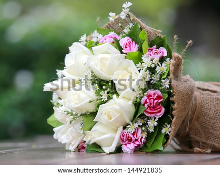 beautiful bouquet of bright white rose flowers, on table with green background - stock photo