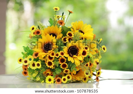 beautiful bouquet of bright yelloe flowers, on  table on green background - stock photo