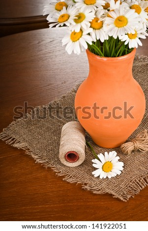 Beautiful bouquet of Chamomile flowers in clay pot on wooden table - stock photo