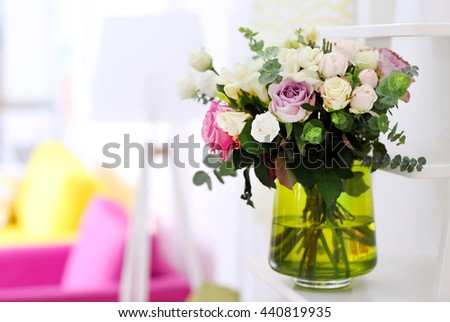 Beautiful bouquet of colourful roses in glass vase - stock photo