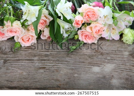 Beautiful bouquet of different flowers on a wooden table - stock photo