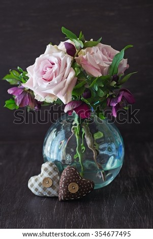 Beautiful bouquet of flowers on a dark background, decorated with fabric hearts. - stock photo