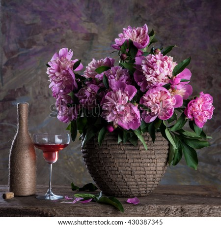 Beautiful bouquet of pink peonies, glass of wine and bottle on a soft multicolored  background - stock photo