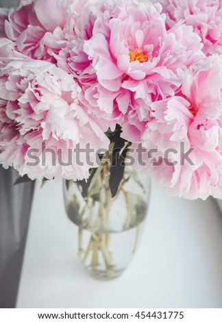 Beautiful bouquet of pink peonies, peony flowers in vase on white window sill, pastel color background. Spring or summer lovely nosegay. Fresh floral, home decor. Trend pink color. Text, copy space - stock photo