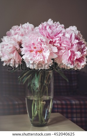 Beautiful bouquet of pink peonies roses flowers in vase on table with sunlight background. Summer time concept. Still life, rustic style, home decor, copyspace - stock photo