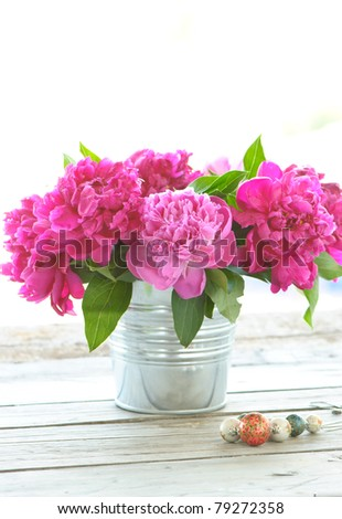 beautiful bouquet of pink peony into a pot on wooden table - stock photo