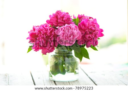 beautiful bouquet of pink peony into a vase on wooden table - stock photo