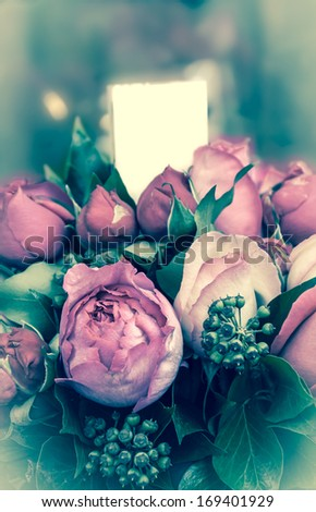 Beautiful bouquet of pink roses and peonies with blank paper attached. Valentines day greeting card. Selective focus and shallow depth of field. Aged photo. Bleached angles. - stock photo