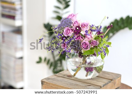 beautiful bouquet of pink roses in a vase on a woody box