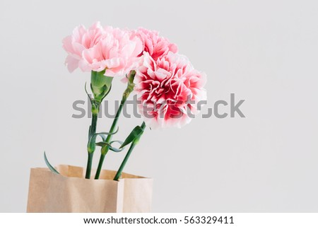 Beautiful bouquet of pink spring flowers in the kraft bag on a light background. Happy International Women's Day, March 8, holiday card.