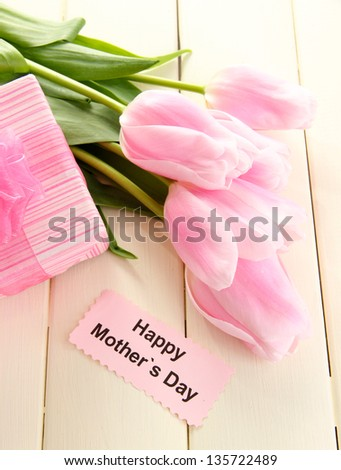 Beautiful bouquet of pink tulips and gift for Mother's Day on white wooden background - stock photo