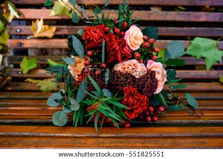 beautiful bouquet of red flowers and green leaves lying on bench