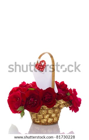 Beautiful bouquet of red roses in a basket. In the white sheet, a greeting card. Isolated