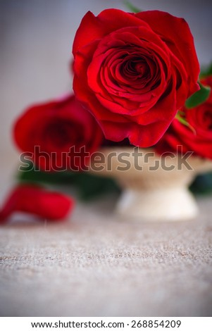 beautiful bouquet of red roses on an old table of burlap - stock photo
