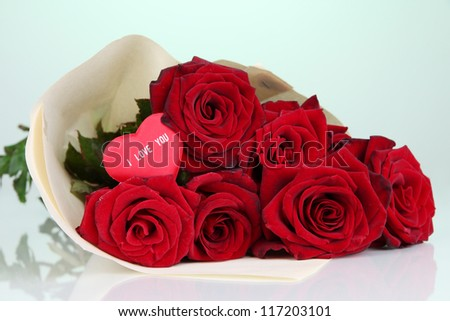 Beautiful bouquet of red roses with valentine on green background