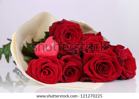 Beautiful bouquet of red roses with valentine on purple background