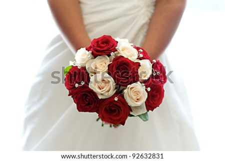 Beautiful Bouquet of Red & White Roses held by a bride - stock photo