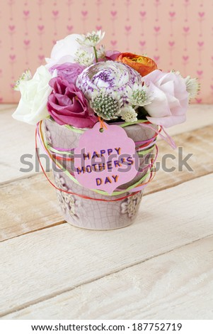 Beautiful bouquet of spring flowers in a flowerpot on a wooden table, for Mother's Day